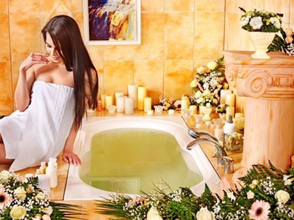 Девушка возле ванны с цветами и свечами